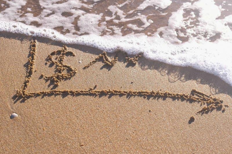 美元的符号和在海沙写的成长曲线图 波浪冲走了题字 免版税库存照片