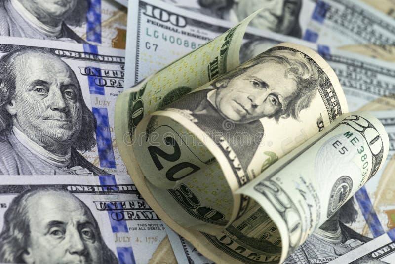 美元票据一半在一百美国美元钞票背景滚动的二十 免版税库存照片