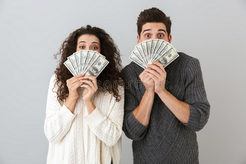美元金钱激动的男人和妇女藏品爱好者的图象,被隔绝在灰色背景 库存图片