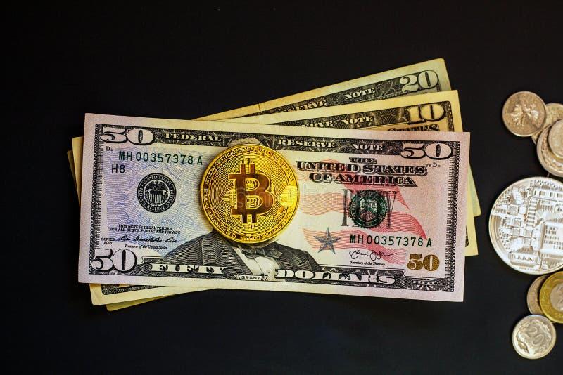 美元钞票和在黑色隔绝的金黄bitcoin硬币 免版税图库摄影