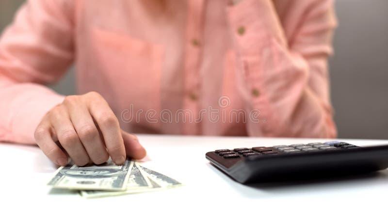美元钞票和计算器在沉思夫人桌前面,缺钱 免版税库存照片