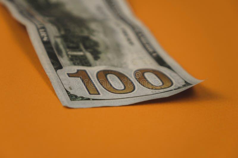 100美元,在橘色背景上 免版税库存图片