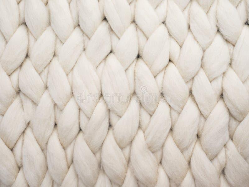 美利奴绵羊的羊毛手工制造被编织的大毯子,超级大块的毛线,时髦舒适概念 被编织的毯子,美利奴绵羊的羊毛backg特写镜头  免版税库存照片