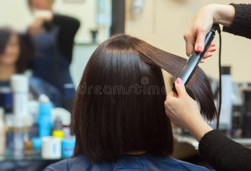 美发师与头发铁对一个女孩,美容院的浅黑肤色的男人排列头发 免版税库存照片