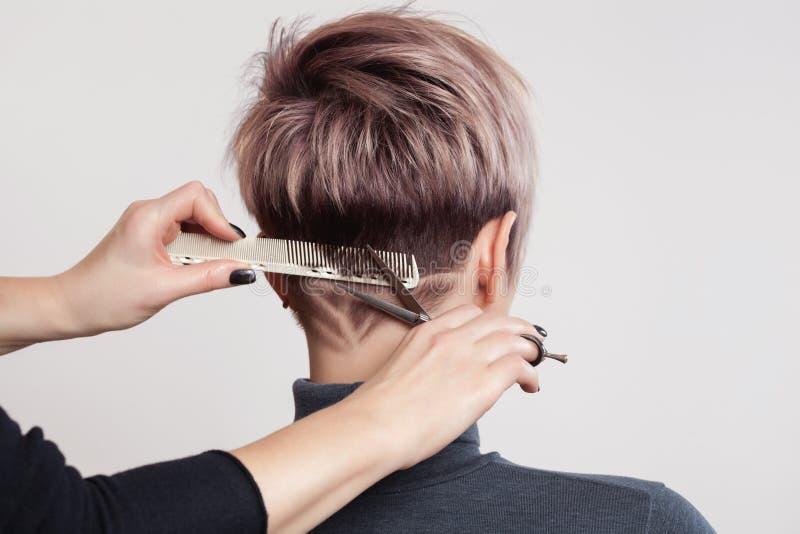 美发师做创造性的理发给美女在美发师 免版税库存照片