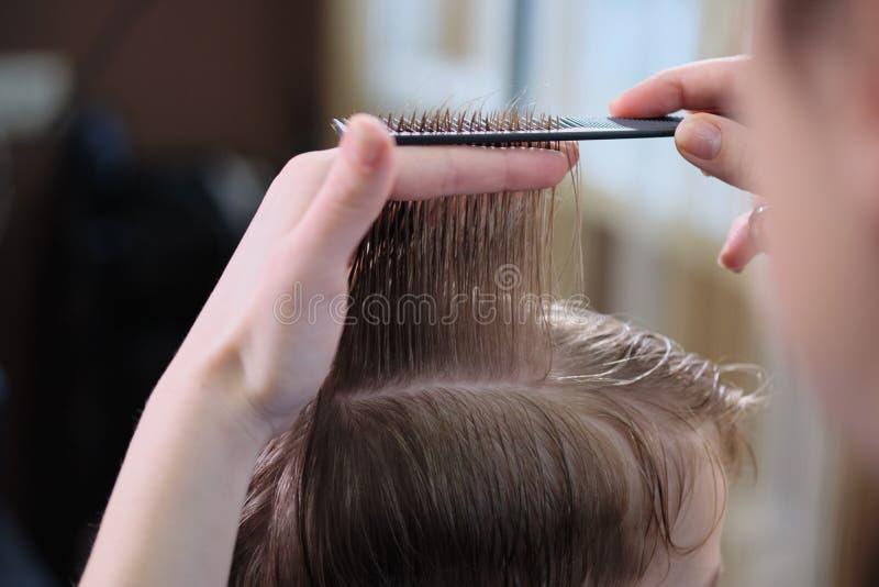 理发店 美发师做发型给有头发剪刀和黑梳子的一个男孩 免版税库存照片