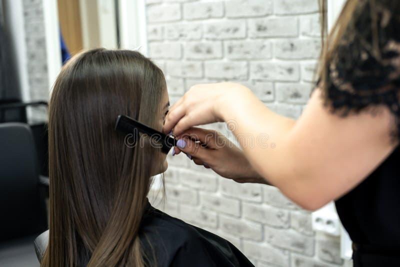 美发师做在一发廊的头发分片有深色的头发的一个女孩的 免版税库存照片