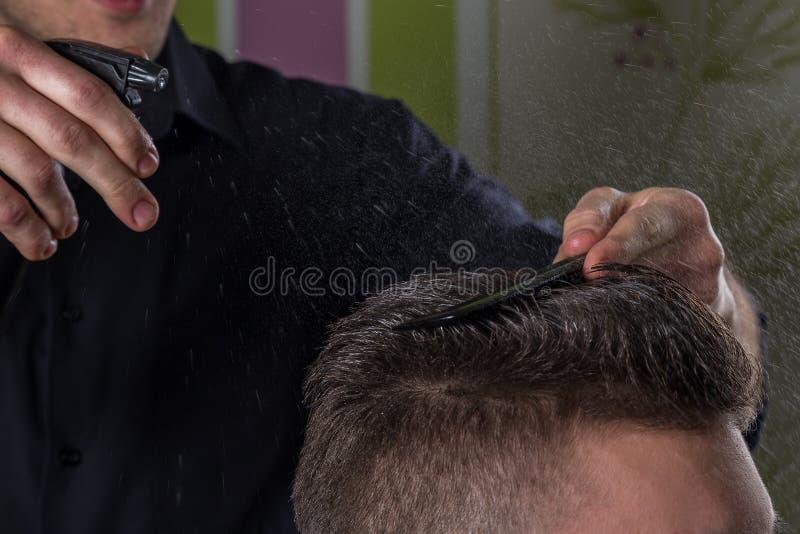 美发师做有客户水和梳子的头发专业理发沙龙的 免版税库存照片