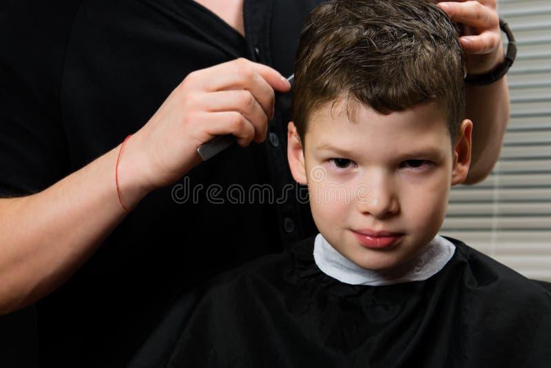 美发师做男孩的理发 图库摄影