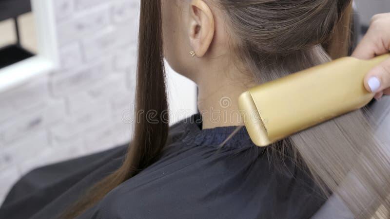 美发师做调直在一个女孩的一发廊的分片和头发有棕色头发的 E 免版税图库摄影