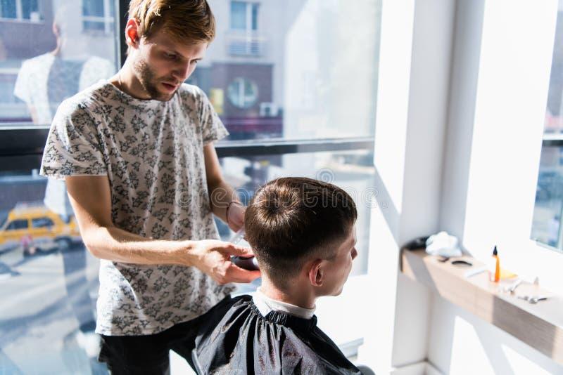 美发师在一把电剃刀和一把梳子帮助下成水平理发在理发店 免版税库存图片