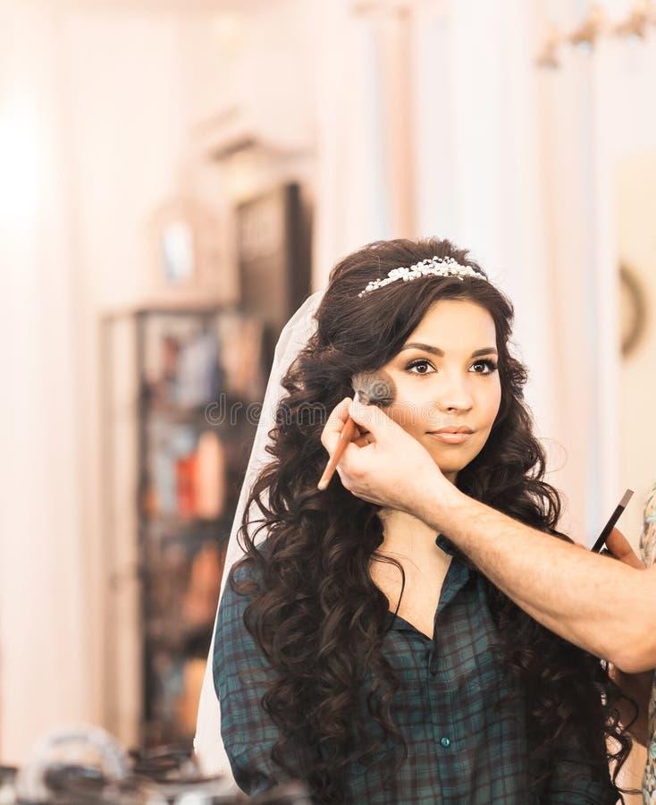 美发师在婚礼之日做构成新娘 免版税图库摄影