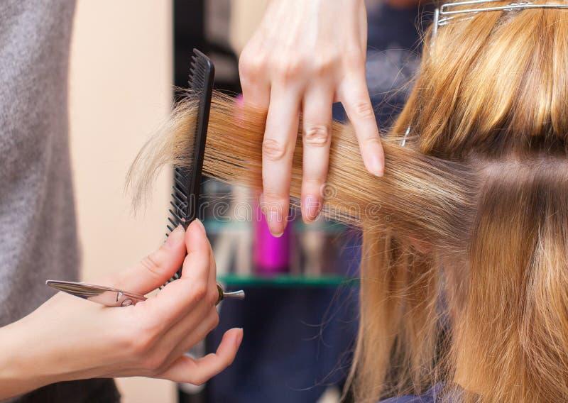 美发师对与头发剪刀的理发做一个女孩 免版税库存图片