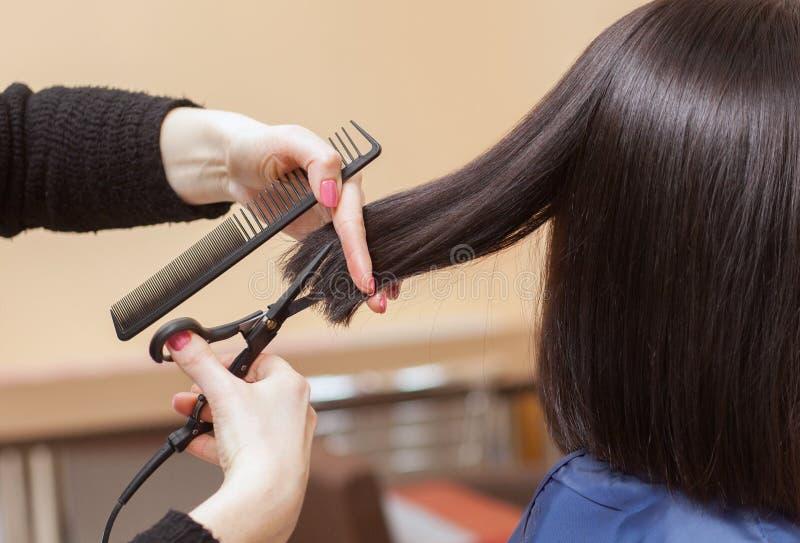 美发师对与头发热的剪刀的理发做一个女孩,浅黑肤色的男人 免版税库存图片