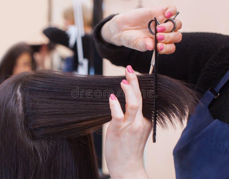 美发师对与头发热的剪刀的理发做一个女孩 免版税图库摄影