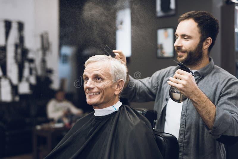 美发师对发型做有灰色头发的一个老人在理发店 免版税库存照片