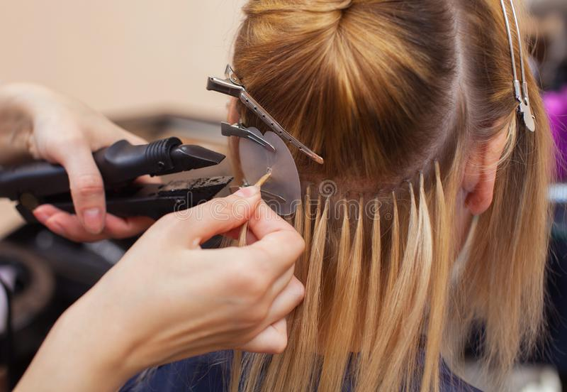 美发师对头发引伸做一个女孩,美容院的一个金发碧眼的女人 库存照片