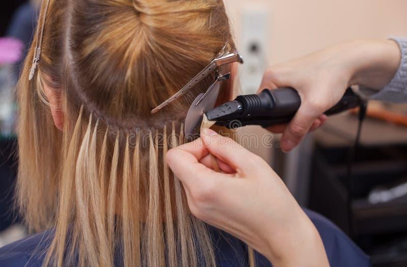 美发师对头发引伸做一个女孩,美容院的一个金发碧眼的女人 免版税图库摄影
