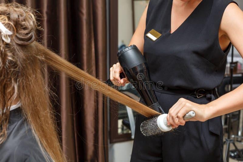 美发师干毛发给有Hairdryer的客户 免版税库存照片