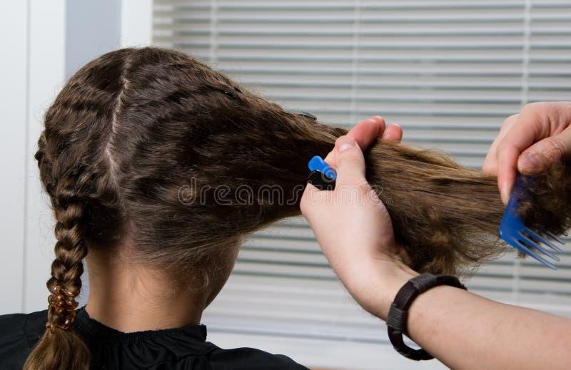 美发师把第二条猪尾编成辫子给孩子,有卷发的 免版税库存照片