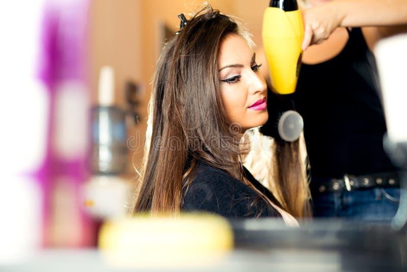 美发师有一hairdryer的干毛发在美容院 免版税库存照片