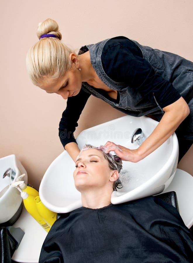 美发师洗涤的妇女 免版税库存照片