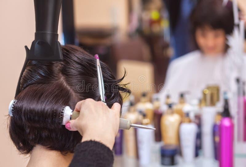 美发师烘干她的头发一个深色的女孩 免版税库存图片