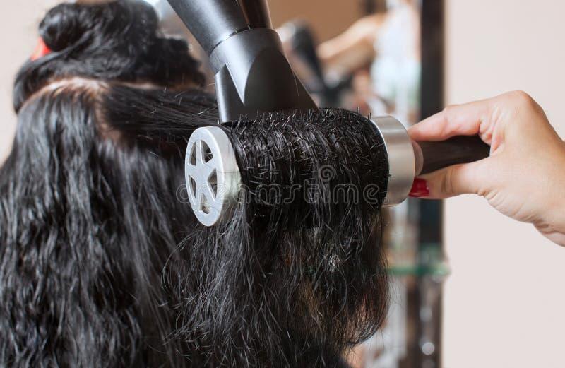 美发师烘干她的头发美容院的一个深色的女孩 免版税库存图片