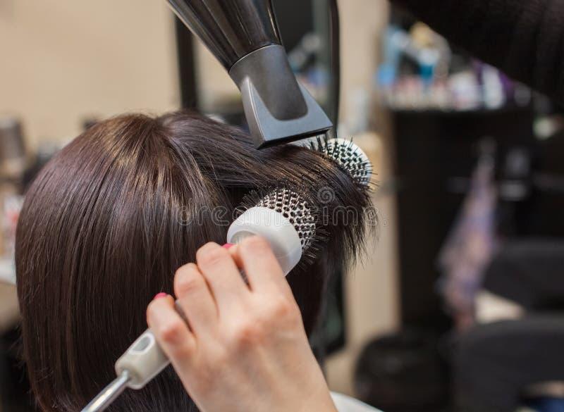 美发师烘干她的头发一个深色的女孩 库存图片