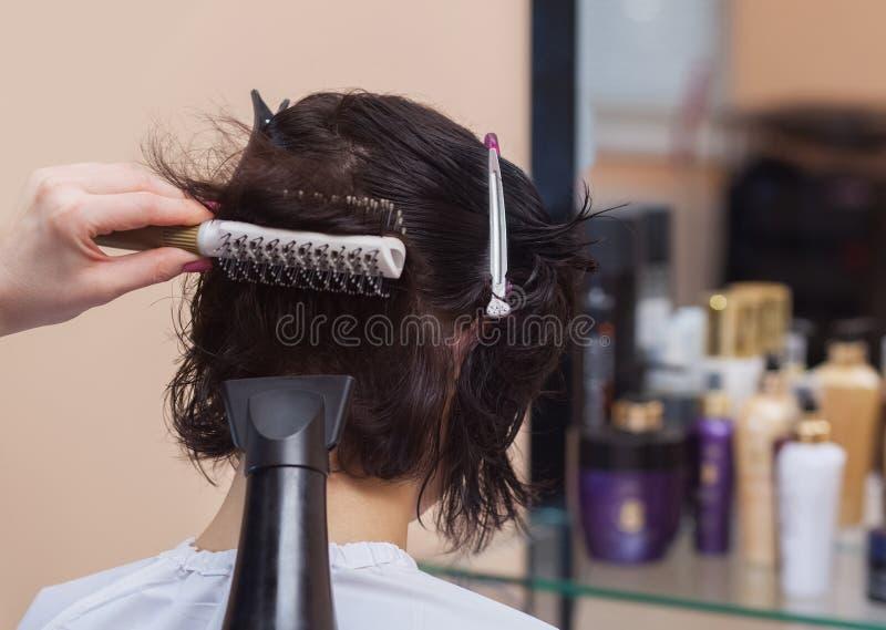 美发师烘干她的头发一个深色的女孩 库存照片