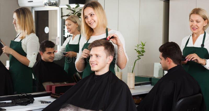 美发师的白肤金发的美发师服务少年 图库摄影