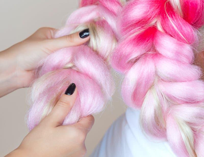 美发师编织与桃红色kanekalons美丽的金发碧眼的女人的辫子 免版税库存照片