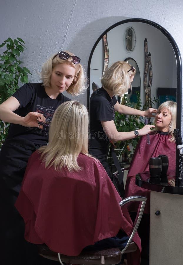 美发师罗斯托夫On唐,俄罗斯,2016年10月6日,做一位新的美发师的理发的美发师的一名白肤金发的妇女 Refl 免版税库存照片