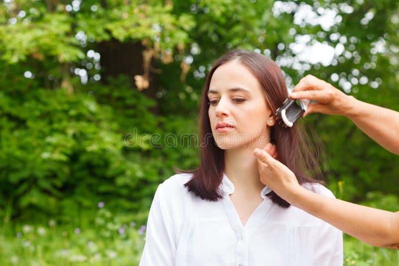 美发师美发师梳有发刷的年轻女人头发 免版税库存照片
