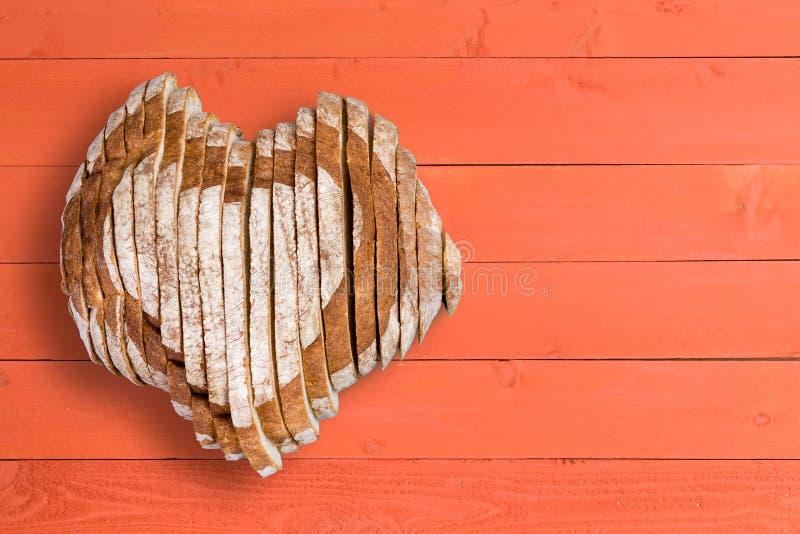 美味的大面包塑造了作为在橙色铣板的心脏 免版税库存照片