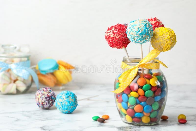 美味的明亮的蛋糕在玻璃瓶子充分流行在桌上的糖果 库存图片