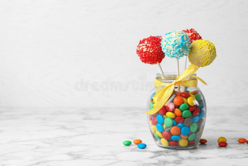 美味的明亮的蛋糕在玻璃瓶子充分流行在桌上的糖果 免版税库存图片