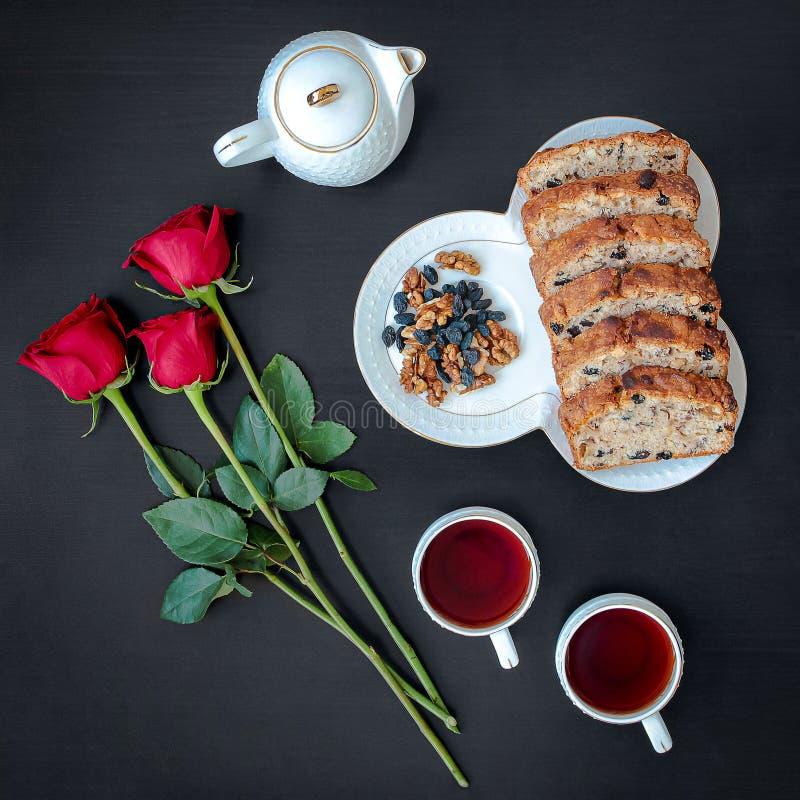 美味的自制蛋糕卷,配有茶具,黑色背景上有红玫瑰,顶部景色 免版税库存照片