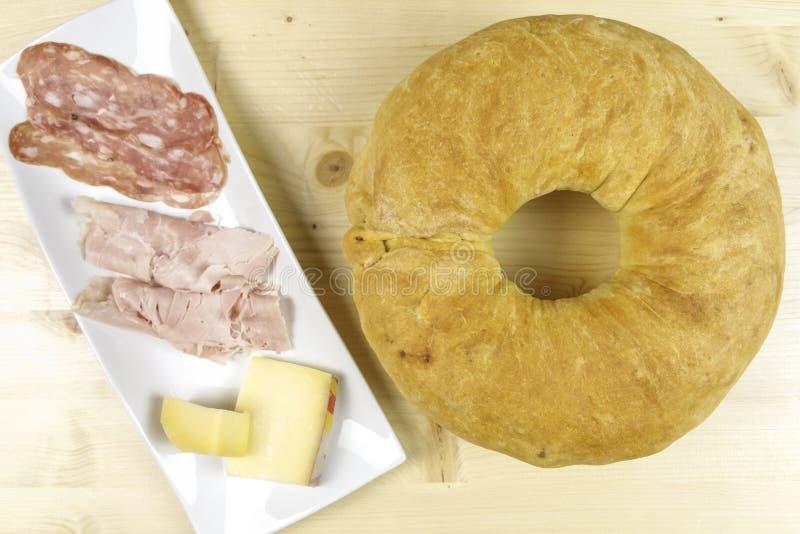 美味蛋糕用蒜味咸腊肠、火腿和乳酪在木背景 免版税库存照片