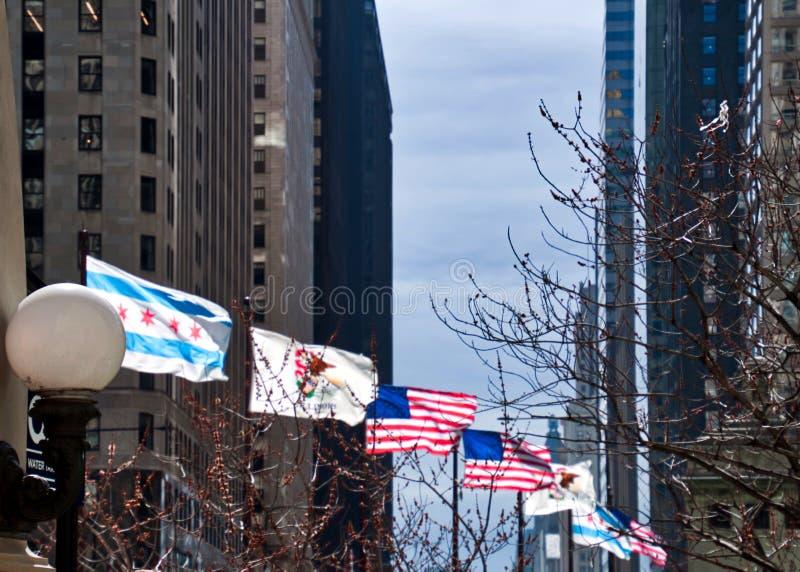 美国、伊利诺伊和芝加哥旗子在沿密执安大道桥梁的一个大风天飞行在冬天 图库摄影