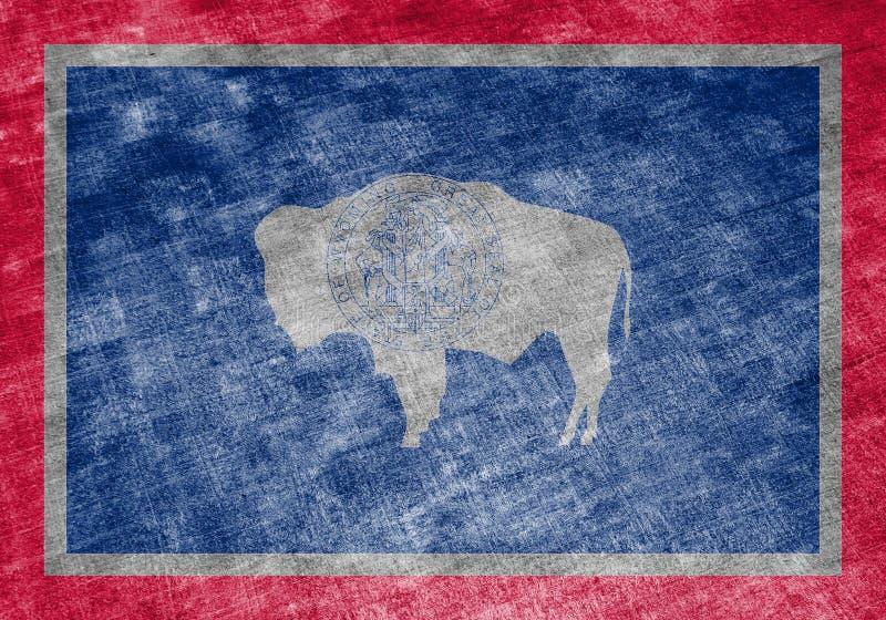 美国各州怀俄明的国旗反对一块灰色纺织品旧布的在蓝色红色不同颜色的独立的那天  皇族释放例证