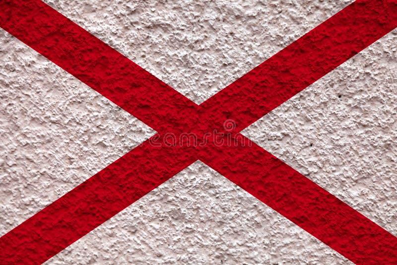 美国各州阿拉斯加的国旗对有石表面的灰色墙壁在蓝色的颜色的独立的那天 免版税库存图片