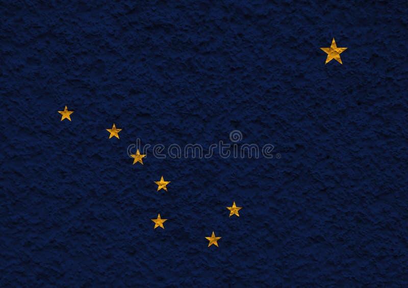 美国各州阿拉斯加的国旗对有石表面的灰色墙壁在蓝色的颜色的独立的那天 库存图片