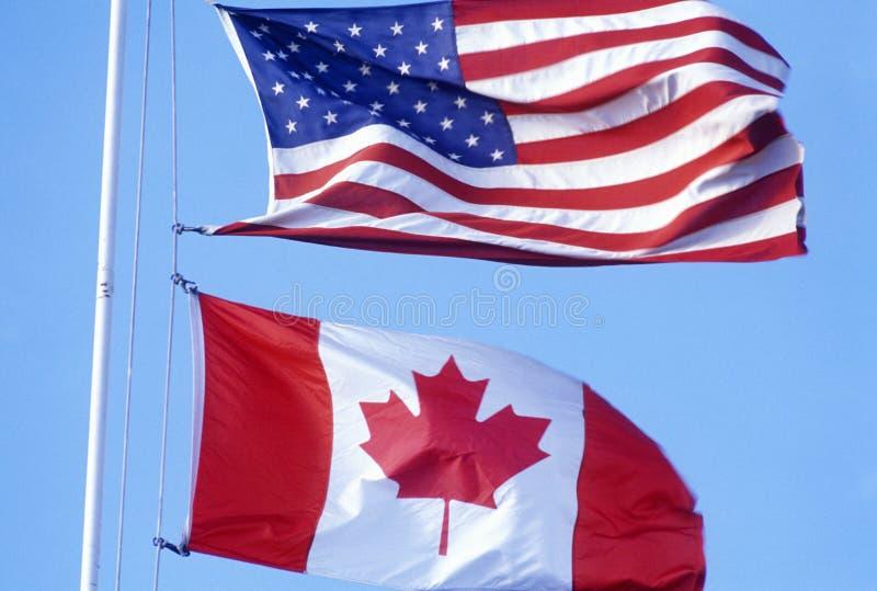 美国和加拿大旗子在加拿大美国边界 免版税库存照片