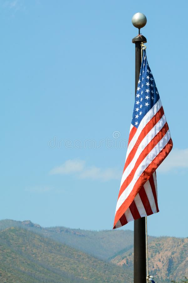 美国国旗、星条旗下垂在清楚的天空的外部 免版税图库摄影