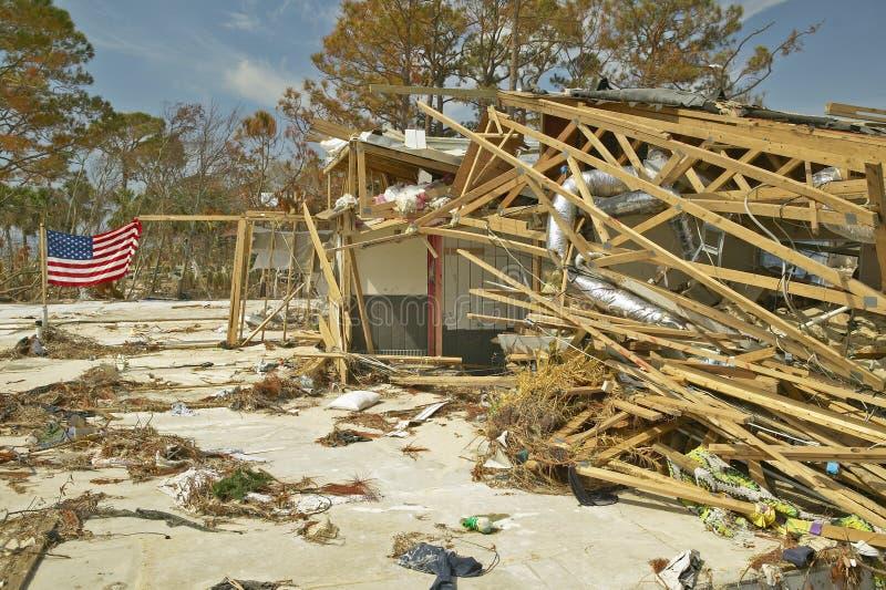 美国国旗在与残骸的风挥动在房子前面由飓风伊冯沉重击中了在彭萨科拉佛罗里达 库存照片