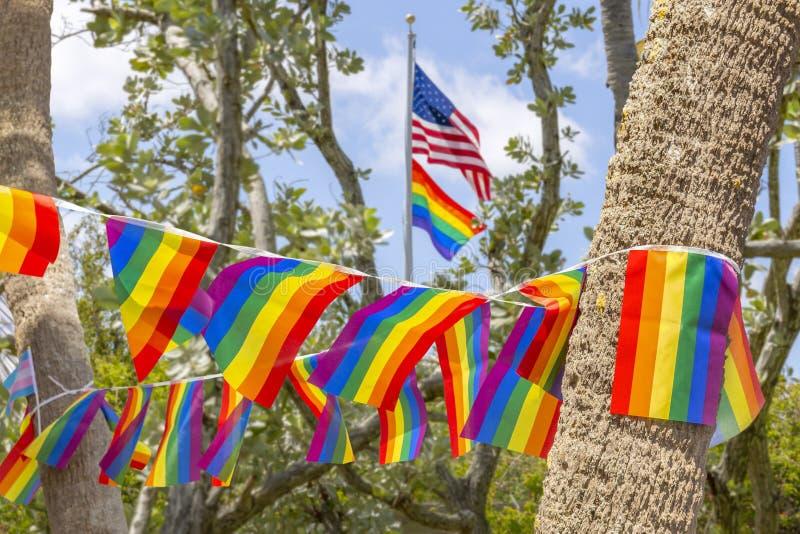 美国国旗在同性恋自豪日旗子的横幅上飞行高 库存图片