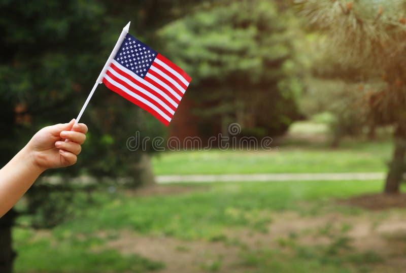 美国国旗在她的手美国独立日上,国旗纪念日概念 免版税库存照片