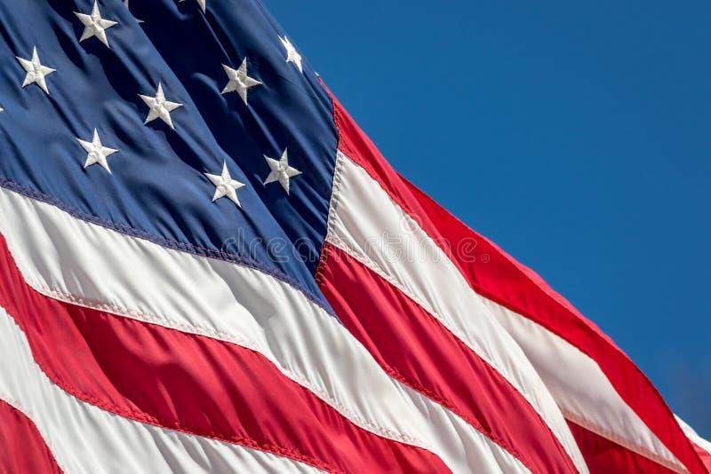 美国国旗用星条旗波浪装饰了在风反对蓝天 图库摄影