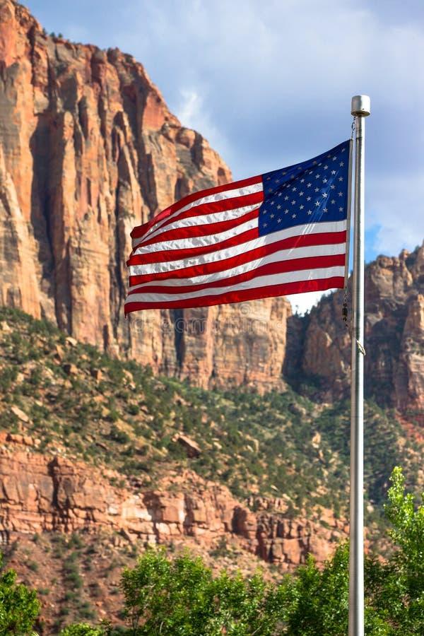 美国国旗的垂直的图片与山的在背景中 库存照片